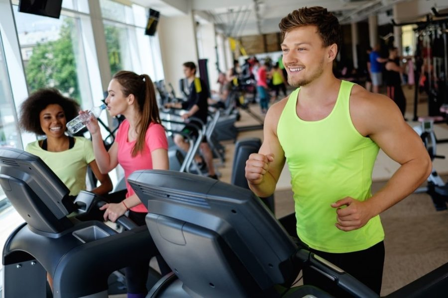 Man and women walking on treadmills at gym