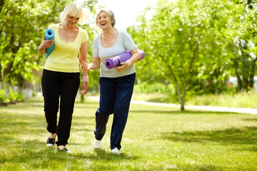 Senior women walking in park with yoga mats