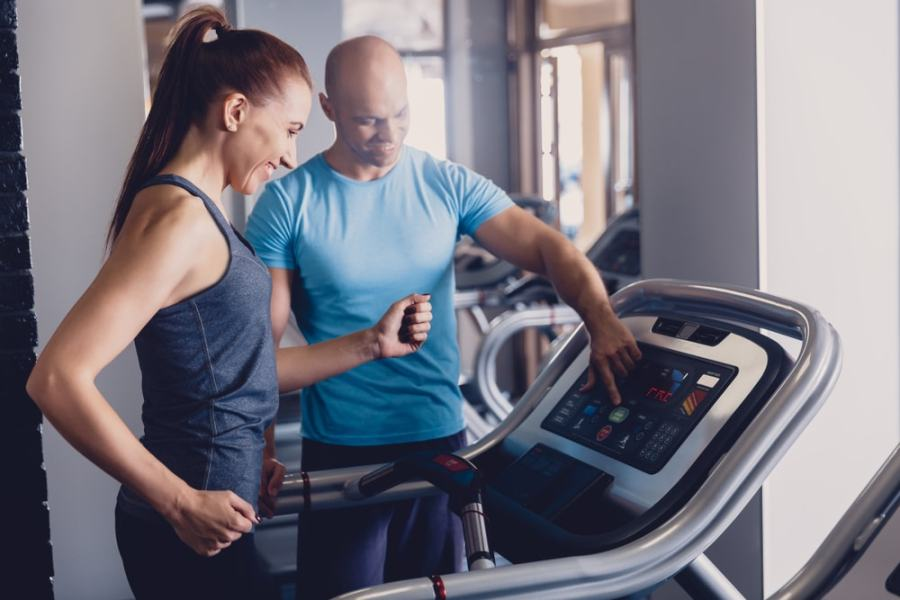Coach helping woman running on treadmill