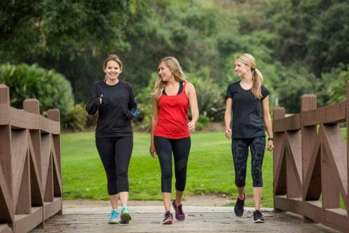 3 women fitness walking across bridge in park