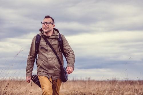 Man hiking in a grassy field