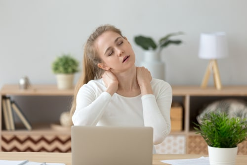 Woman with sore neck working on computer