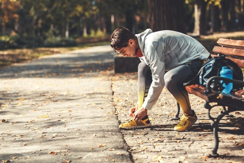 Man tying shoes on a park bench during walk