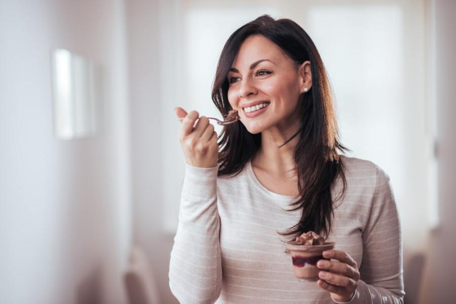 Woman eating a dessert at home
