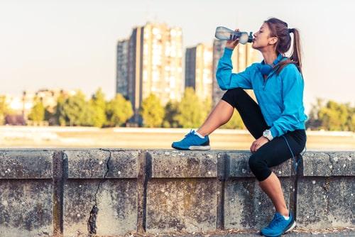 Woman taking a water break during outdoor walk
