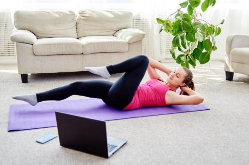 Woman doing pilates on mat at home