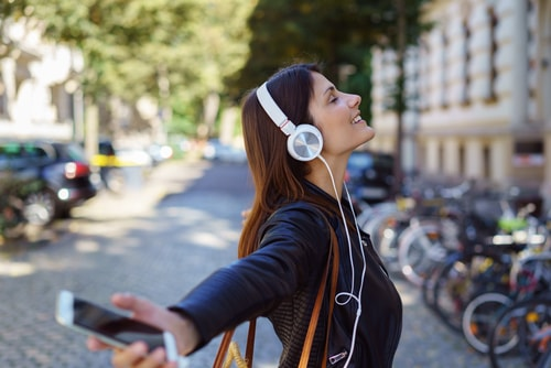 Woman happily listening to music during a walk