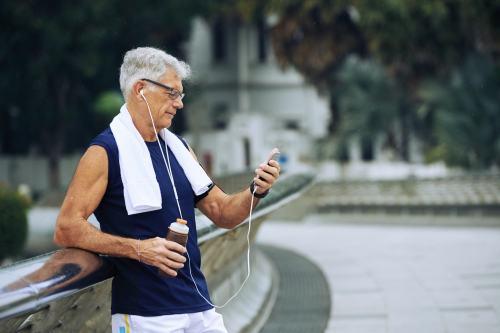 Senior man checking phone during a walk or run