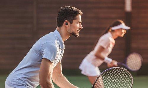 Man playing tennis wearing Tranya earbuds