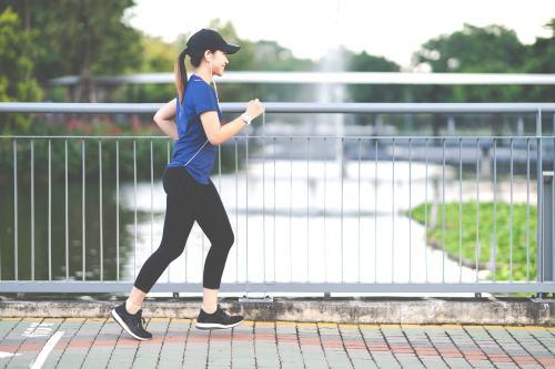 Woman walking for fitness on a bridge
