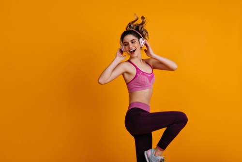 Woman doing dance moves with orange background