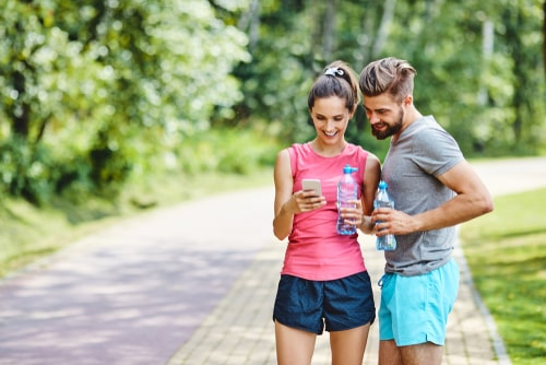 Couple on a fitness walk checking smartphone