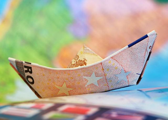 argent billet plié en forme de petit bateau sur un fond coloré