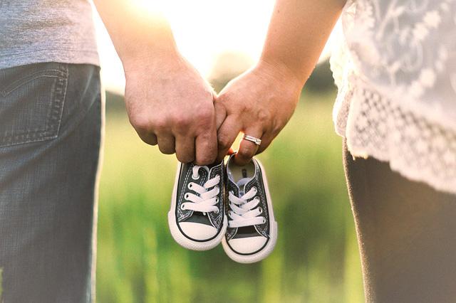 Couple tenant une paire de mini basquettes de leur futur enfant