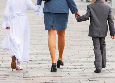 maman tenant par la main un communiant en aube et un petit garçon en costume