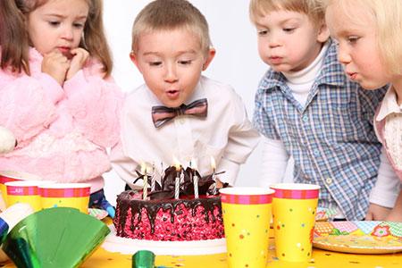 garçon avec un noeud papillon qui souffle ses bougies d'anniversaire