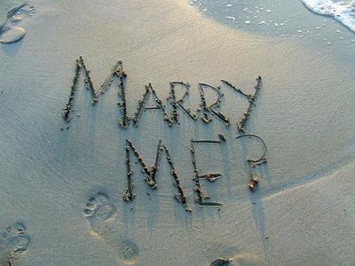 marry me écrit sur le sable d'une plage