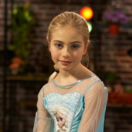 Petite fille en robe de reine des neiges coiffée en tresse comme Elsa d'Arendelle