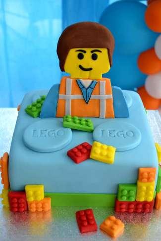 gâteau d'anniversire lego bleu avec le célèbre personnage ouvrier de lego emmett