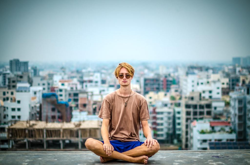 man wearing sunglasses meditating in front of a city skyline