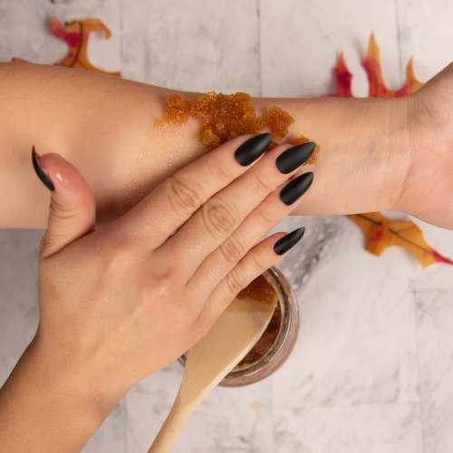 a hand using the pumpkin sugar scrub