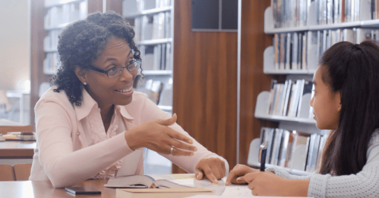 Teacher Instructing Student In Library
