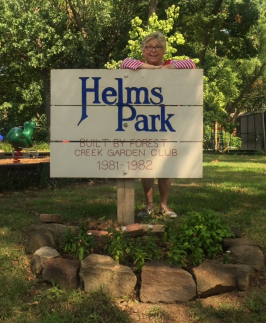 Sherry in front of Helms Park, named after her for her efforts in transforming the vacant lot into a beautiful park next to the swimming pool.