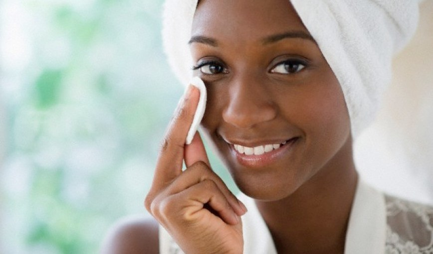 31 Jul 2013 --- Black woman wiping face with cotton pad --- Image by © JGI/Jamie Grill/Blend Images/Corbis