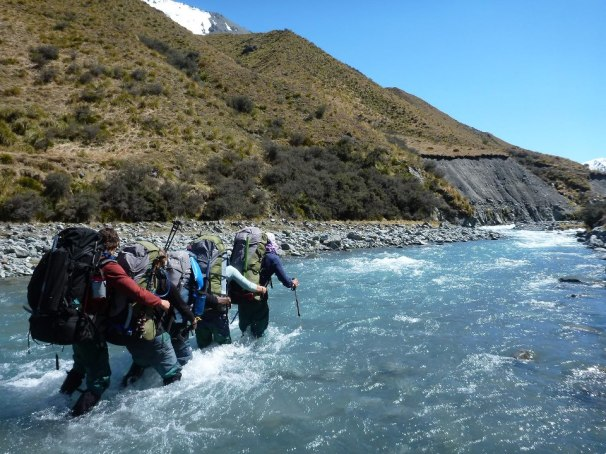 A group of people walking over a river crossing highland to represent the power behind expedition behavior