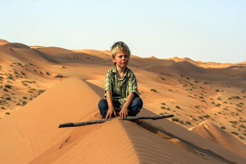 Oman: Junge auf Düne (P. Valentin)