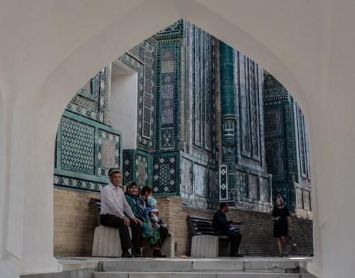 Menschen sitzen vor einer Moschee in Usbekistan