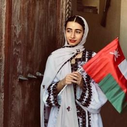 Oman: Flagge des Sultanats in der Hand eines Schulmädchens in traditoneller Kleidung