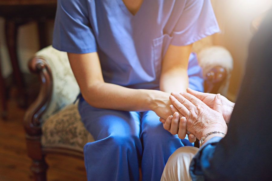 Shot of a resident being consoled by a nurse in a retirement home