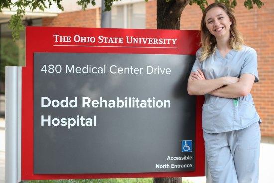 Bethany Frick standing in front of Ohio State University, Dodd Rehabilitation Hospital signage