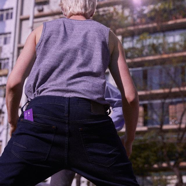 La espalda de un hombre joven jugando baloncesto; lleva un pantalón oscuro y en su bolsillo posterior, una tarjeta de crédito Nu.