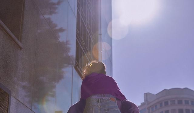 Se ve la espalda de una mujer llevada al tun tun; adelante, el sol da sobre un edificio vidriado. La política de tratamiento de datos de Nu Colombia.