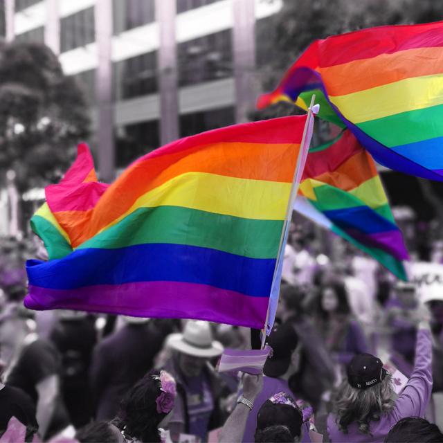 Día del Orgullo LGBTQIA+. Una martc ha callejera con banderas multicolores flameando.