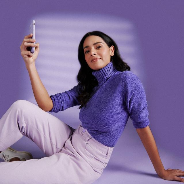 Una usuaria de la app de Nu -cabello oscuro, polera morada- mira a cámara y muestra su celular.