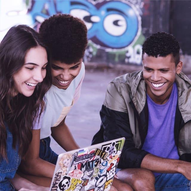 Tres amigos sonriendo frente a computadora