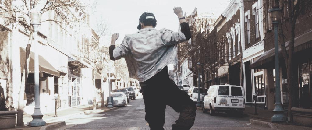 el mejor momento para comprar un auto: joven vestido con mezclilla danza en una calle