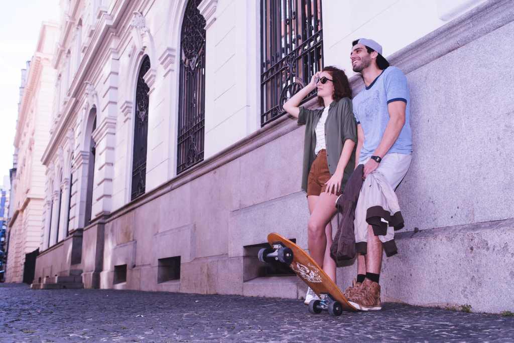 Tarjeta Nu: un hombre y una mujer jóvenes y sonrientes apoyados en la fachada de un edificio antiguo: ella es pelirroja y usa anteojos negros; el usa una gorra hacia atrás y pisa el extremo de un skate.
