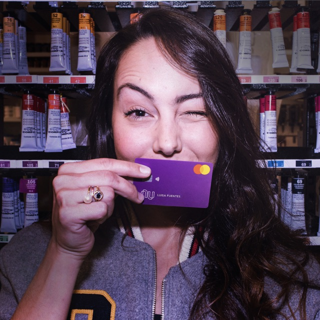 Tarjeta de crédito Nu: el retrato de una chica joven y morocha con una tarjeta morada que cubre la parte inferior de su rostro y guiñando el ojo izquierdo.