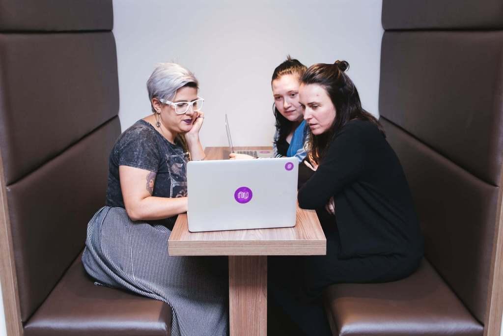 Metodología ágil con tres compañeras de trabajo físicamente diversas, observan una computadora con atención.