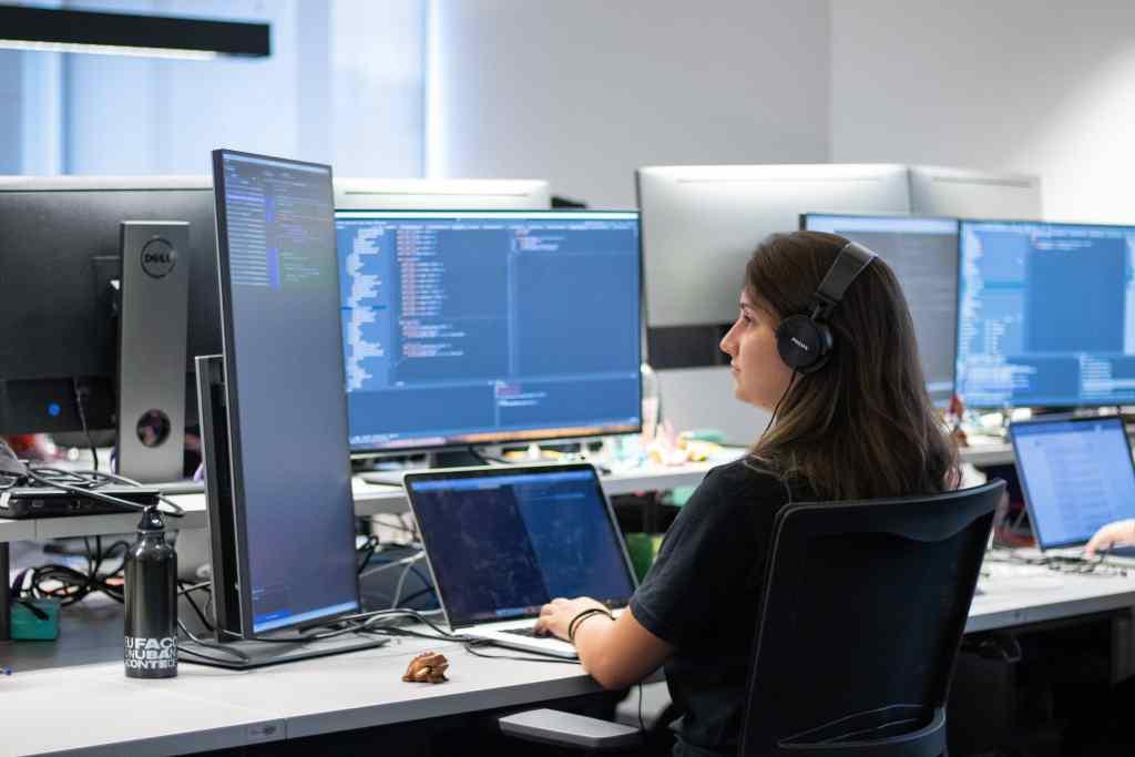 Una chica con auriculares trabaja frente a una computadora y tres pantallas