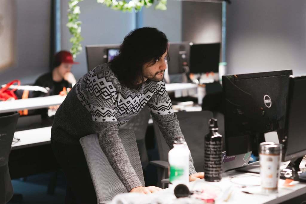 Un hombre joven con pullover gris parado frente a su computadora, apoya los brazos en la mesa y observa la pantalla.