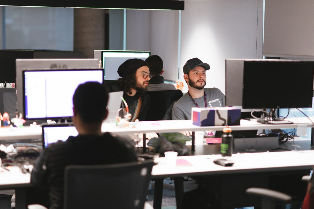 Dos hombres jóvenes con gorro miran atentamente una pantalla.