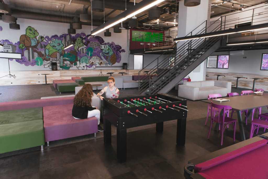 Una gran sala con juegos y sillones verdes y violetas, con un graffiti de fondo y dos mujeres jóvenes hablando entre sí sentadas.