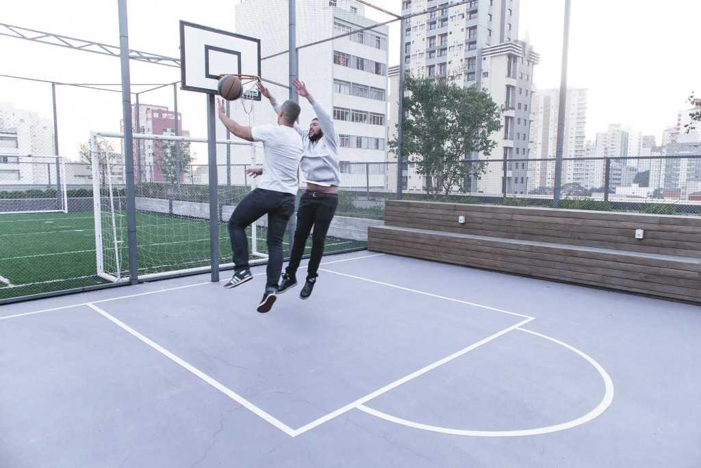 Dos hombres jóvenes vestidos con jeans saltan frente a un aro de basquetbol: uno intenta embocar el balón, el otro intenta impedirlo.