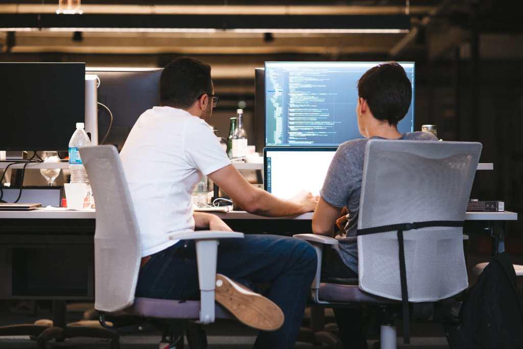 Dos hombres trabajan frente a una computadora de pantalla negro con símbolos blancos en segundo plano.