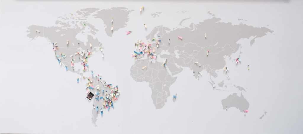 Mapa mundial pintado en gris sobre una pared blanca, con papelitos de colores muestra las nacionalidades que tienen los empleados de Nubank. Tencent